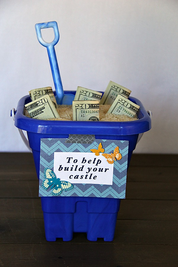Creative Ways To Give Money As A Gift-a sand bucket full of money for the soon to be new homeowner to build their new castle