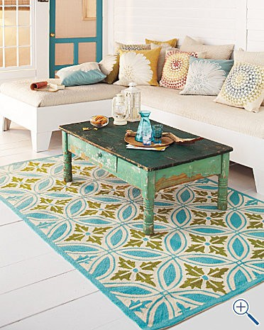 one the nicest things to put on a front porch is a sofa with a colorful rug and table.