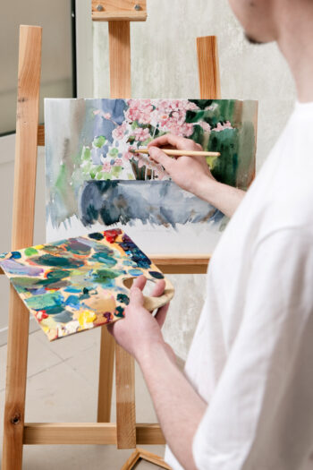 A painter painting a piece of art on a wooden easel.